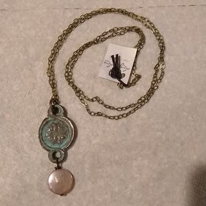 Celtic cross on pendant with flat pearl drop.